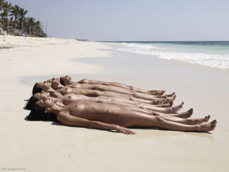 Safadas deitada na areia da praia peladas